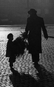 Father and son carrying tree in street